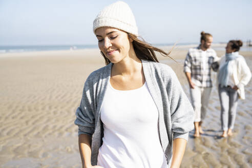 Young woman smiling while walking with boyfriend and mother in background at beach - UUF21670