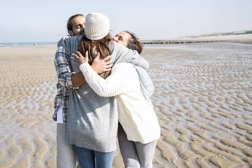 Young woman embracing man and mother while standing at beach - UUF21673