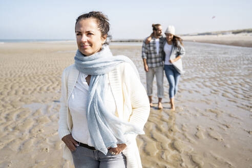Woman with hands in pockets looking away while walking with couple in background at beach - UUF21682