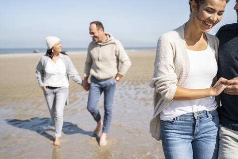 Smiling woman holding man hand while walking with couple in background at beach - UUF21694