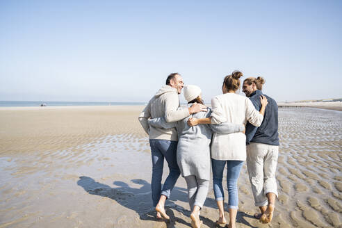 Family with arms around talking while walking together at beach - UUF21700