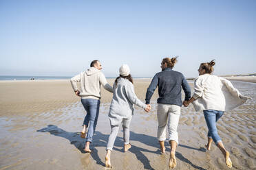 Family holding hands while running on beach - UUF21718