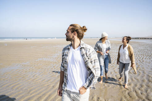 Man looking away while walking with women talking in background at beach - UUF21730