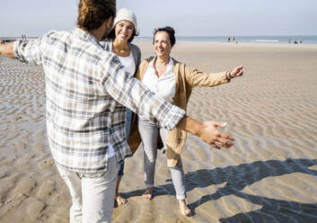 Man standing with arms outstretched to hug women while standing at beach - UUF21733