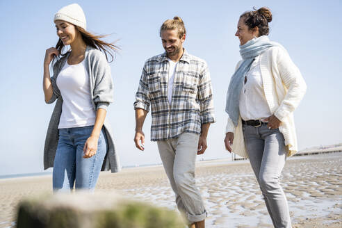 Smiling woman walking with boyfriend and mother at beach - UUF21742