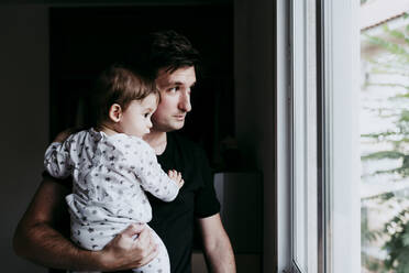 Father carrying son while standing looking through window at home - EBBF00887