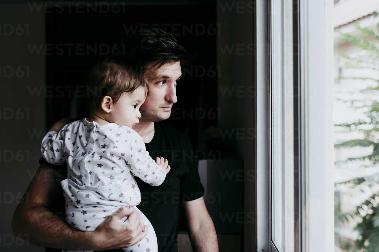 Vater trägt Sohn, während er zu Hause durchs Fenster schaut - EBBF00887 - Eva Blanco/Westend61