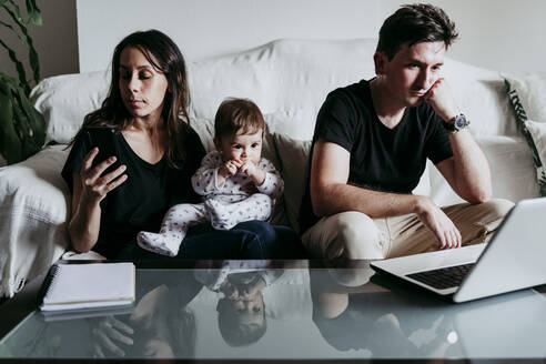Mother using smart phone while father working on laptop with son sitting at home - EBBF00893