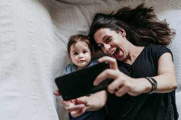 Mother and son taking selfie on smart phone while lying down in bedroom at home - EBBF00917