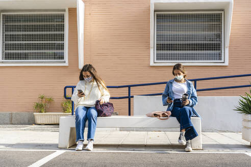 Female teenage friends social distancing while using smart phone sitting on concrete bench - ERRF04569