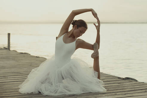 Full body flexible classic ballet female dancer in elegant white dress performing sensual pose on wooden pier against blurred sea in summer evening - ADSF16694