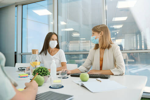 Young woman in protective mask making presentation on computer monitor with graphs during business meeting with coworkers in contemporary office space - ADSF16709