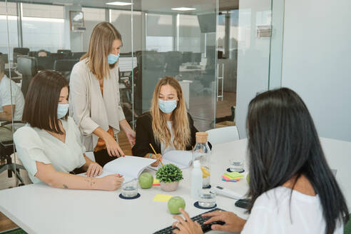 Young female manager in medical mask explaining business idea to coworkers while standing together in modern workspace and discussing project - ADSF16712