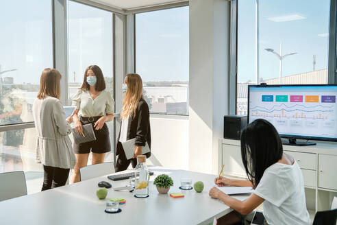 Young female manager in medical mask explaining business idea to coworkers while standing together in modern workspace and discussing project - ADSF16715