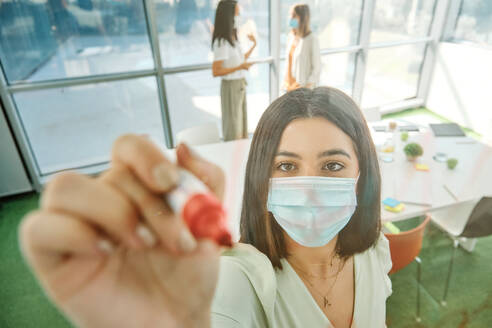 Young female member of business team in protective mask taking notes on glass wall while working with colleagues and searching for solution of business problem in contemporary office - ADSF16721