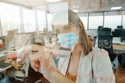 Young female member of business team in protective mask taking notes on glass wall while working with colleagues and searching for solution of business problem in contemporary office - ADSF16724