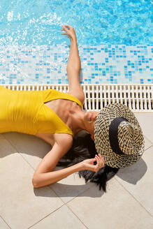 From above full body of unrecognizable slim female in swimsuit and hat lying near swimming pool with clear blue water and enjoying summer holidays in resort - ADSF16745