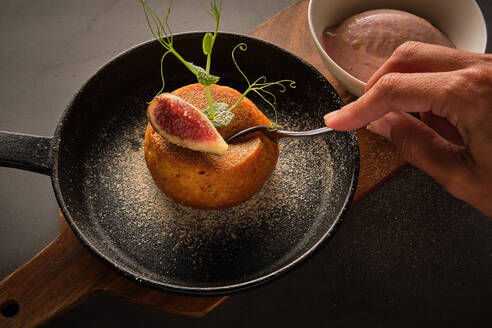 High angle of unrecognizable person eating delicious cake with slice of fig fruit and greenery served in frying pan in cafe - ADSF16754