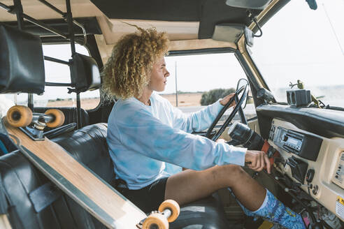 Young blond Afro woman sitting by skateboard while driving old off-road vehicle - DAMF00571