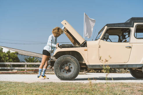 Young woman examining off-road vehicle while standing with open hood on sunny day - DAMF00574