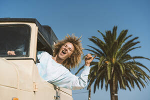 Happy blond woman gesturing while sitting in old off-road vehicle on sunny day - DAMF00577