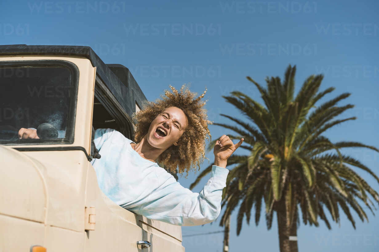 Happy blond woman gesturing while sitting in old off-road vehicle on sunny day - DAMF00577 - David Agüero Muñoz/Westend61