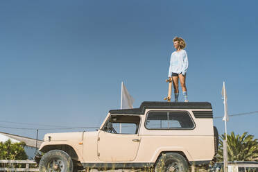 Young woman holding skateboard while standing on old off-road vehicle against blue sky during sunny day - DAMF00580