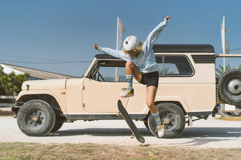 Woman skateboarding against old vehicle on sunny day - DAMF00583