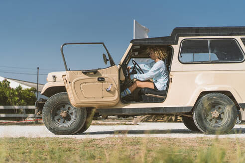 Woman sitting in old off-road vehicle on sunny day - DAMF00586