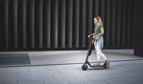 Woman standing on electric push scooter against metal wall on sunny day - HMEF01102
