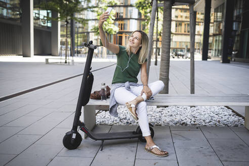 Smiling mid adult woman listening music and taking selfie while sitting on bench in city - HMEF01108