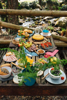 High angle of old wooden table with assorted dishes served for cozy picnic in forest in Valle del Jerte - ADSF16835