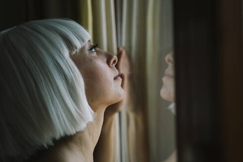 Woman looking up while standing by window at home - AFVF07344