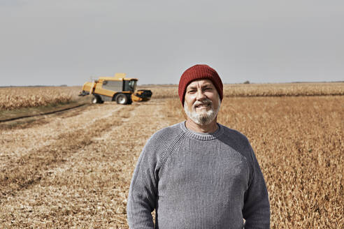 Smiling farmer standing at field during sunny day - ZEDF03965