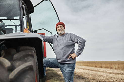 Confident farmer standing with hand on hip by tractor at farm - ZEDF03974