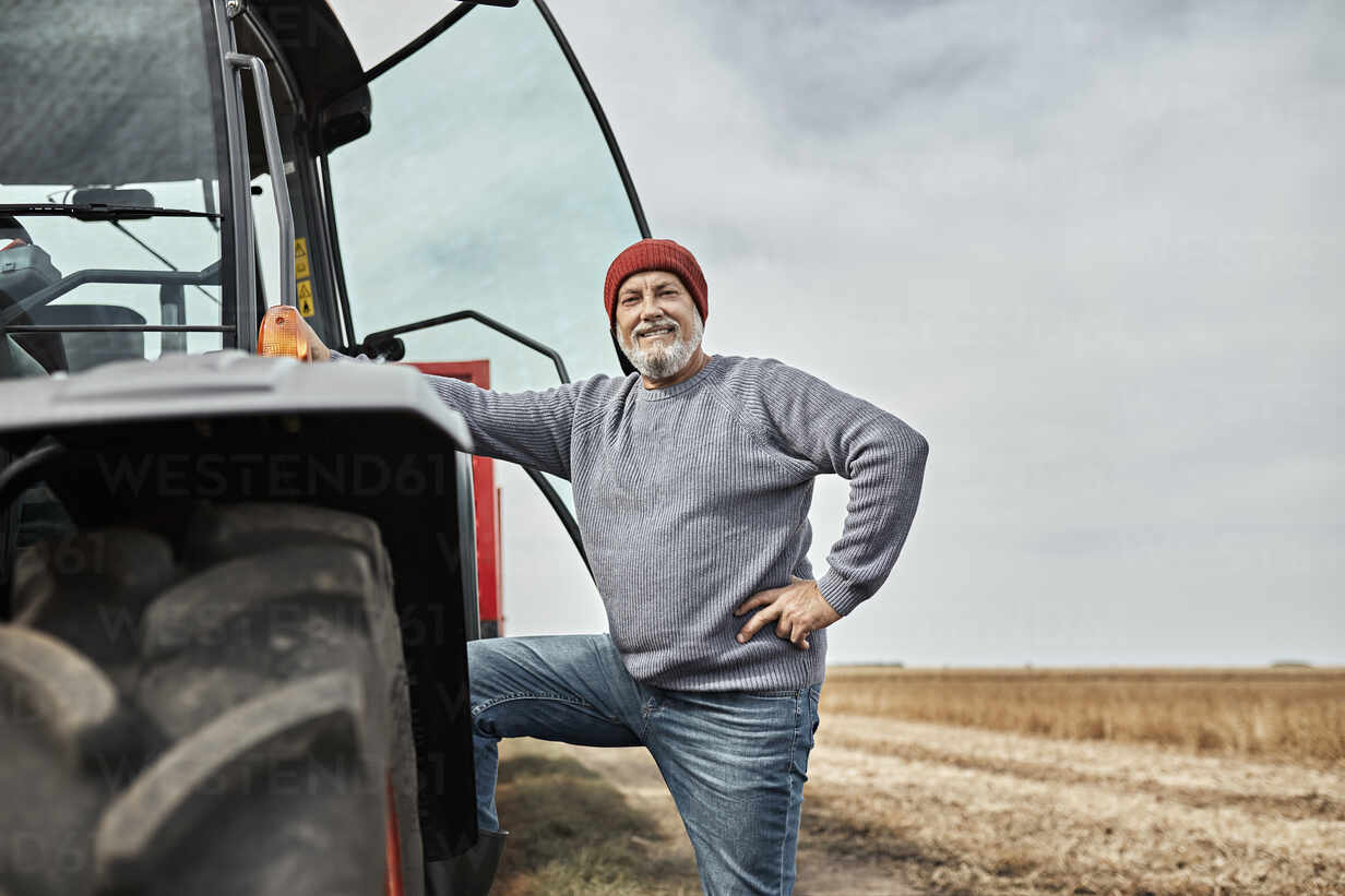Confident farmer standing with hand on hip by tractor at farm - ZEDF03974 - Zeljko Dangubic/Westend61