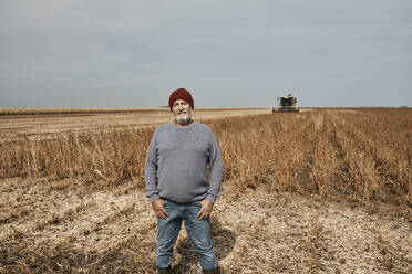 Smiling farmer standing with hands in pockets at soybean farm - ZEDF03980