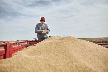 Farmer using digital tablet while standing on tractor against clear sky - ZEDF03992