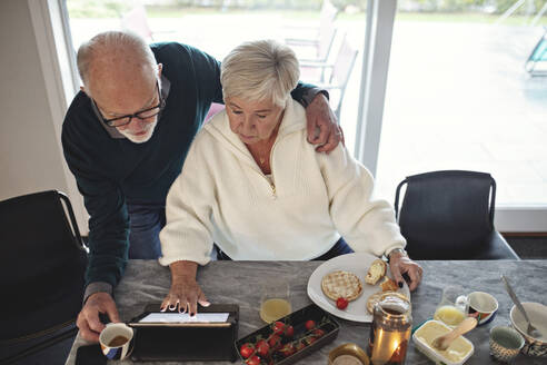 High angle view of senior couple looking at digital tablet while sitting by dining table in living room - MASF19973