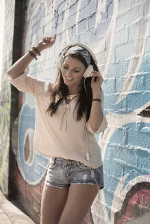 Beautiful woman dancing while listening music through headphones against wall with graffiti - AJOF00301