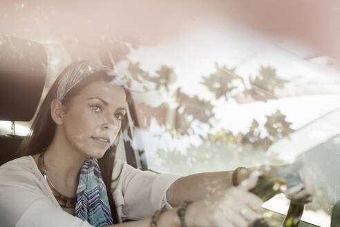 Young woman driving car seen through windshield - AJOF00304