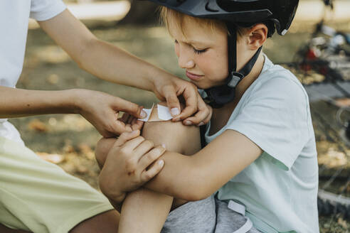 Boy putting bandage on younger brother knee sitting in public park - MFF06376