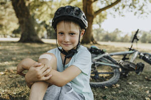 Boy sitting with bandage on knee in pubic park on sunny day - MFF06379