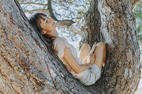 Mature woman relaxing on tree in public park - MFF06403