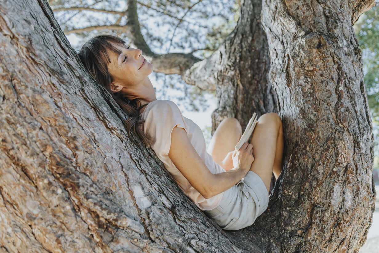 Mature woman relaxing on tree in public park - MFF06403 - Mareen Fischinger/Westend61