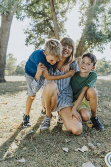 Happy mother embracing sons in public park on sunny day - MFF06415