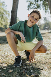 Boy crouching in pubic park on sunny day - MFF06421
