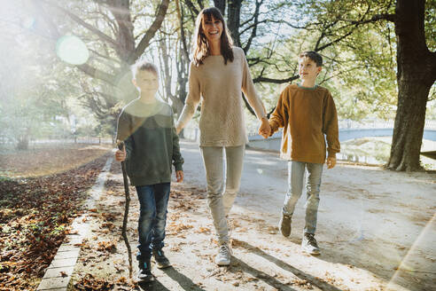 Happy mother and sons walking in public park on sunny day - MFF06430