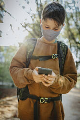 Boy using smart phone wearing protective face mask while standing in public park - MFF06439