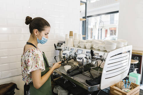 Young woman with face mask making coffee while standing in kitchen at coffee shop - XLGF00595